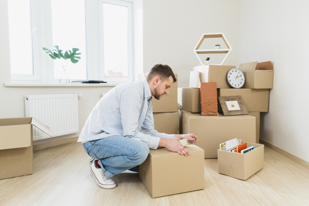 young-man-packing-cardboard-boxes-home_23-2148059989